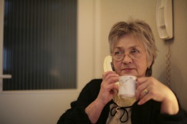 A woman with a cup of tea on the phone to our helpline