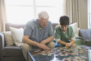 Grandfather and grandson solving puzzle in living room