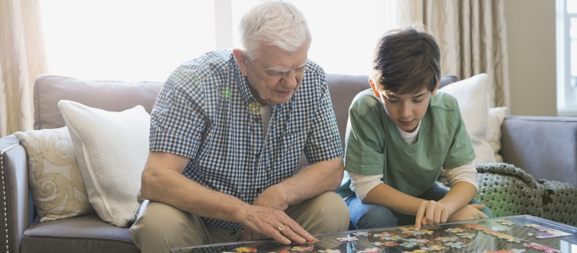 Grandfather and grandson solving a jigsaw puzzle