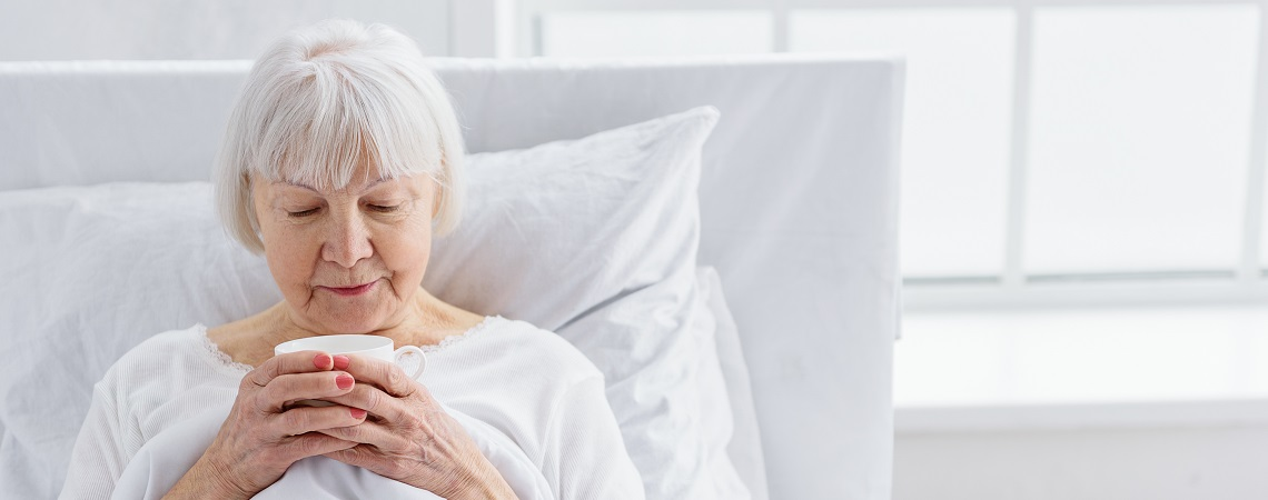 person with dementia drinking a hot drink