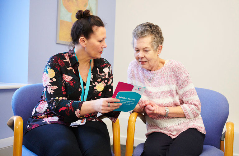 Admiral Nurse with carer looking at information leaflets