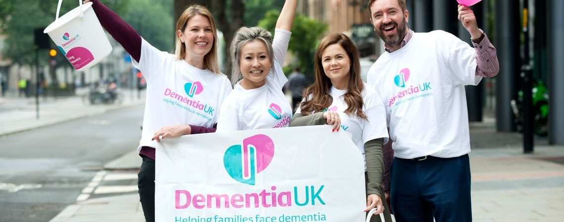 fundraisers holding Dementia UK flag and balloons