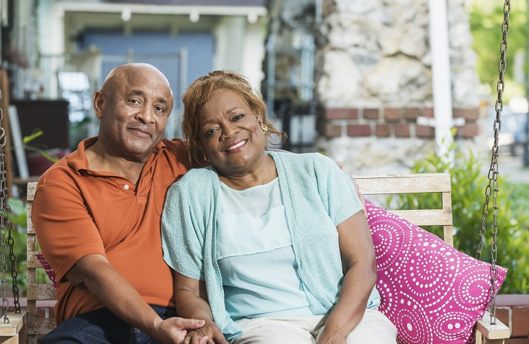 Senior couple sitting on porch swing holding hands