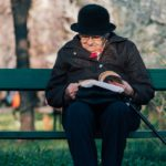 Lady reading a book on a bench