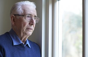 Isolated man looking out of window